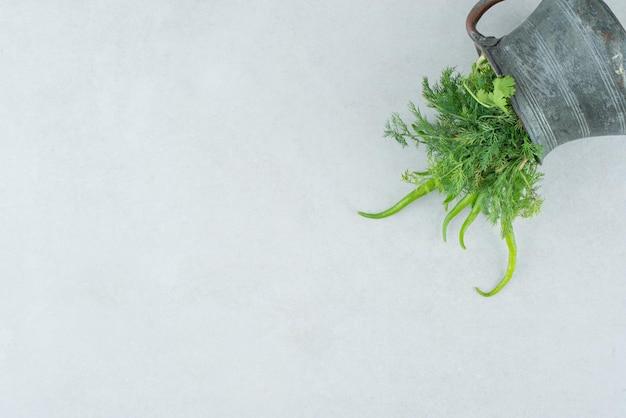 Verse greens en spaanse peperpeper uit klassieke mok.