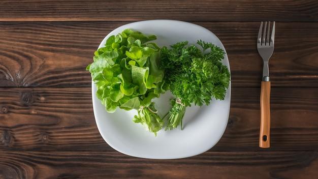 Verse greens op een witte plaat en een vork op een houten tafel. het concept van gezond eten. plat leggen.