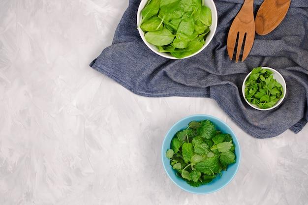 Verse greens voor een salade op cementachtergrond: spinazie, munt en peterselie op donkerblauwe handdoek met houten lepels, copyspace