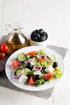 Verse griekse salade gemaakt van cherry tomaat, notensla, rucola, feta, olijven, komkommers, ui en kruiden.
