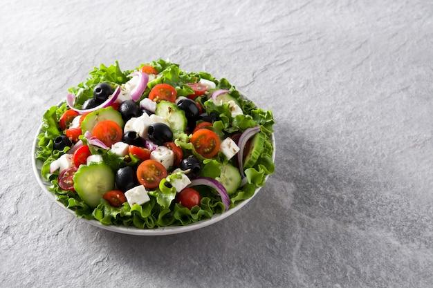 Verse griekse salade in plaat met zwarte olijven, tomaat, feta-kaas, komkommer en ui op grijze achtergrond kopie ruimte