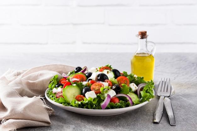 Verse griekse salade in plaat met zwarte olijven, tomaat, feta-kaas, komkommer en ui op grijze achtergrond