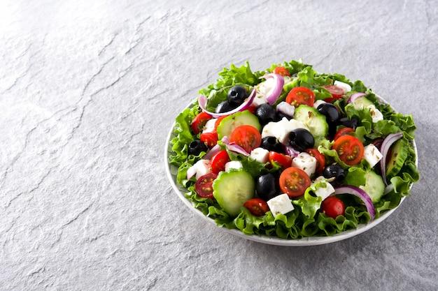 Verse griekse salade in plaat met zwarte olijven, tomaat, feta-kaas, komkommer en ui op grijze copyspace