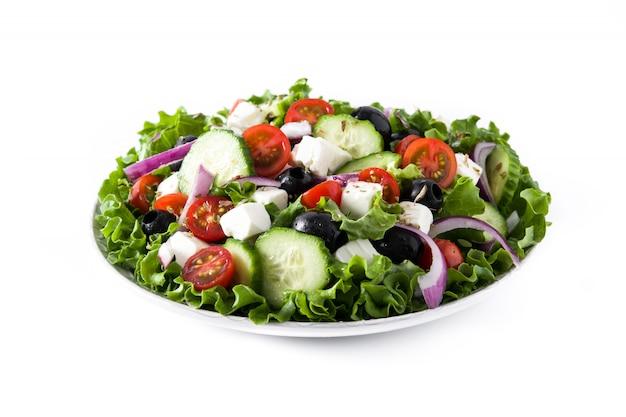 Verse griekse salade in plaat met zwarte olijven, tomaat, feta-kaas, komkommer geïsoleerd op een witte achtergrond.