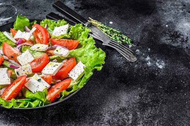Verse griekse salade met groenten en fetakaas in een plaat. zwarte achtergrond. bovenaanzicht. kopieer ruimte.