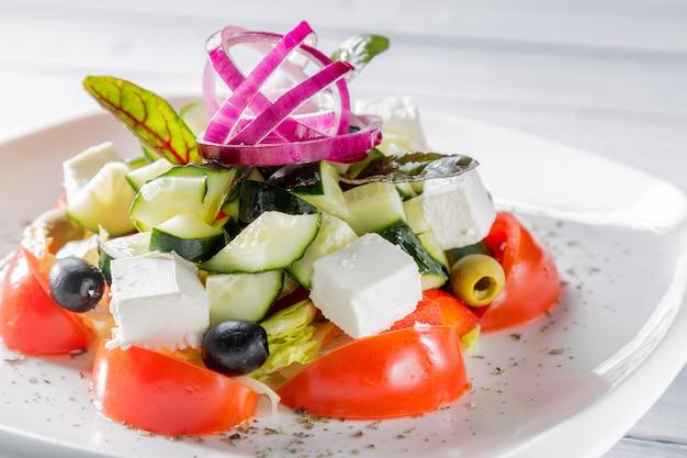 Verse griekse salade op witte plaat met ui