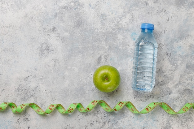 Verse groene appel, meetlint en fles zoet water op grijs beton