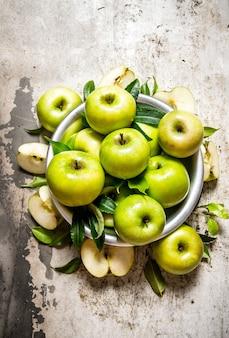Verse groene appels in een schotel op een rustieke achtergrond. bovenaanzicht
