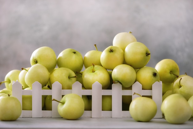 Verse groene appels in houten kist op lichtgrijs. vrije ruimte