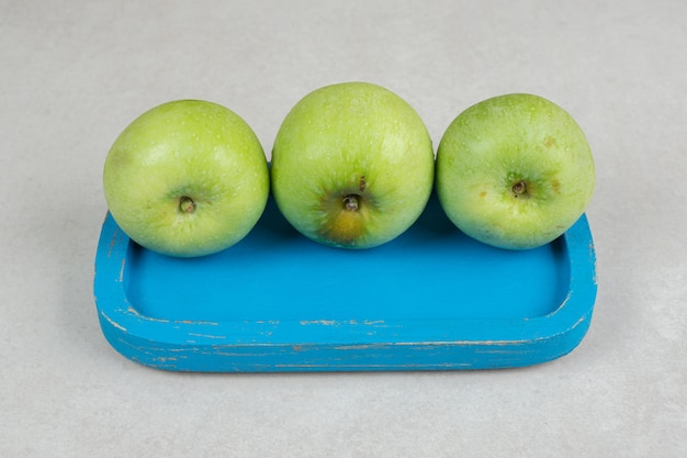 Verse groene appels op blauw bord