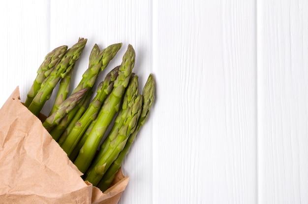 Verse groene asperges in papieren boodschappentas op witte houten tafel tafel.