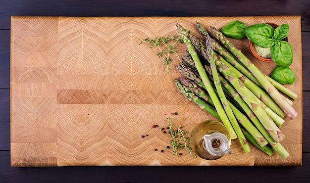 Verse groene asperges met kruiden op een rustieke houten tafel
