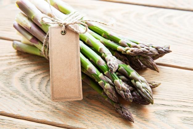 Verse groene asperges met lege tag op oude houten tafel.