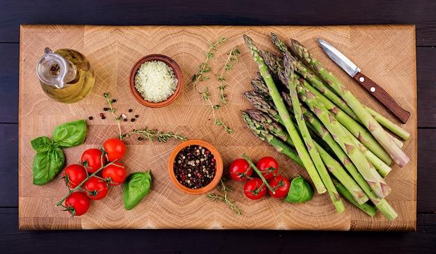 Verse groene asperges met tomaten en kruiden op een rustieke houten tafel