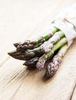 Verse groene asperges op oude houten tafel.