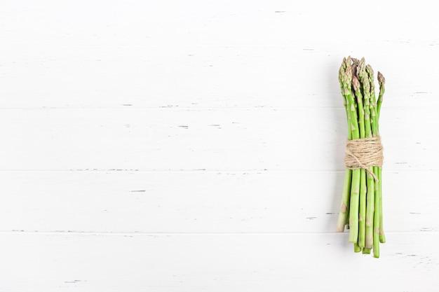 Verse groene asperges op witte houten oppervlak