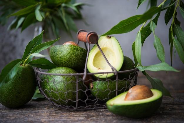 Verse groene avocado met bladeren op houten ruimte
