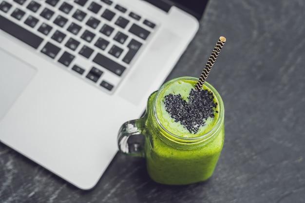 Verse groene banaan smoothie met spinazie en sesamzaad hart op een houten tafel naast een laptop