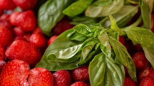Verse groene basilicum en aardbeien voorbereid voor het maken van jam