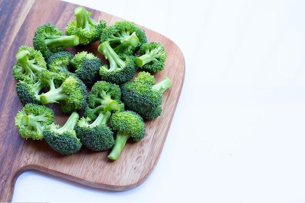 Verse groene broccoli op houten snijplank op wit.