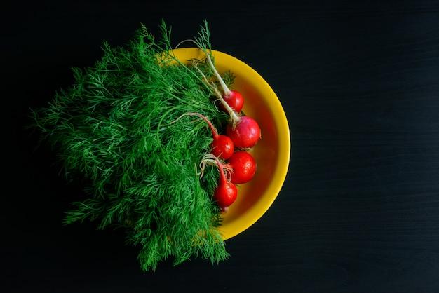 Verse groene dille en radijs op gele plaat, zwarte achtergrond, landbouwproducten, tuinieren.