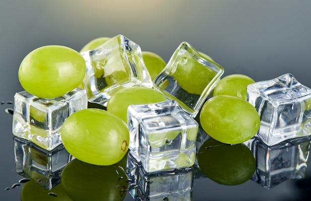 Verse groene druiven met waterdruppels en ijsblokjes op grijze achtergrond