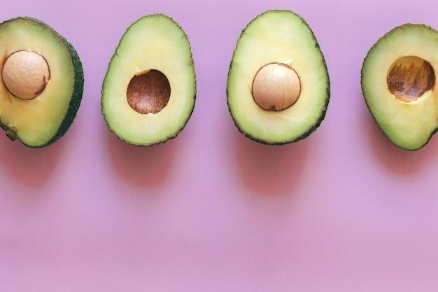 Verse groene gehalveerde en gesneden avocado geïsoleerd op een roze achtergrond, bovenaanzicht, close-up, ruimte voor tekst.