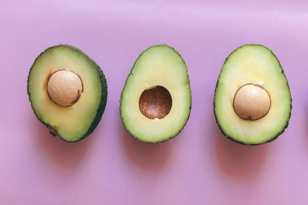 Verse groene gehalveerde en gesneden avocado geïsoleerd op een roze achtergrond, bovenaanzicht, close-up.
