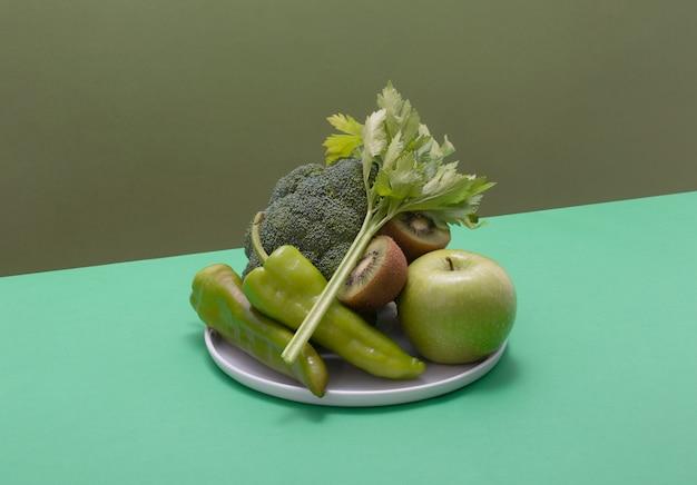 Verse groene groenten en fruit op groene tafel. alkalisch dieetconcept, horizontaal