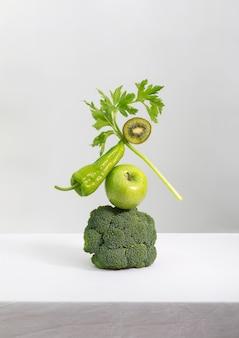 Verse groene groenten en fruit op tafel. evenwicht drijvende voedselbalans