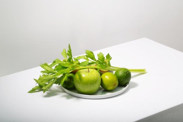 Verse groene groenten en fruit op witte tafel. alkalisch dieetconcept, horizontale oriëntatie