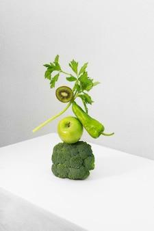 Verse groene groenten en fruit op witte tafel. evenwicht drijvend voedsel