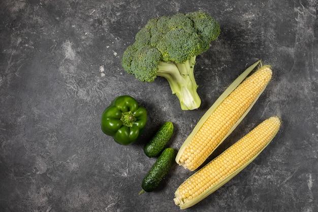 Verse groene groenten op een donkere tafel, bovenaanzicht met kopie ruimte.