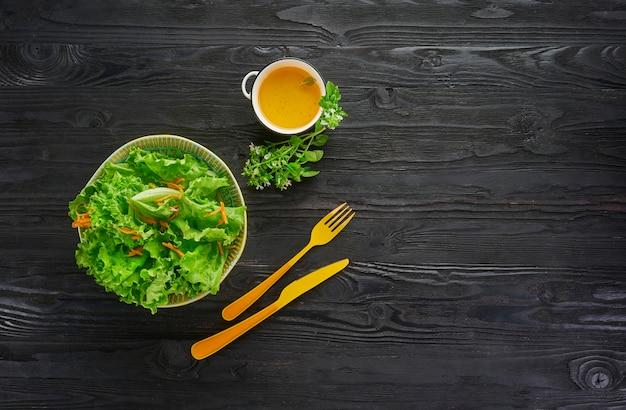 Verse groene groentesalade met sla en wortel in kom met oranje mes en vork op donkere houten lijst