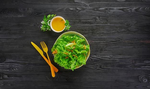 Verse groene groentesalade met sla en wortel in kom met oranje mes en vork op donkere houten tafel, gezond veganistisch eten en dieet concept, bovenaanzicht