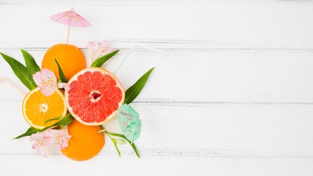 Verse groene installatiebladeren en citrusvruchten onder bloemen