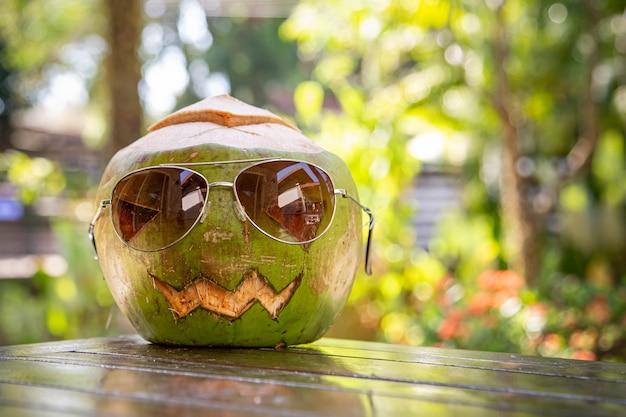 Verse groene kokosnoot met zonnebril in de vorm van halloween pompoen kokosnoot met een gesneden gezicht