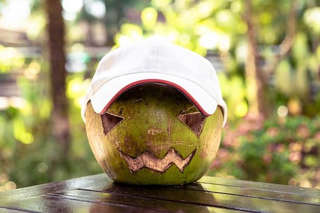 Verse groene kokosnoot op tafel hij draagt een witte baseballpet die erop is uitgehouwen met halloween-symbolen