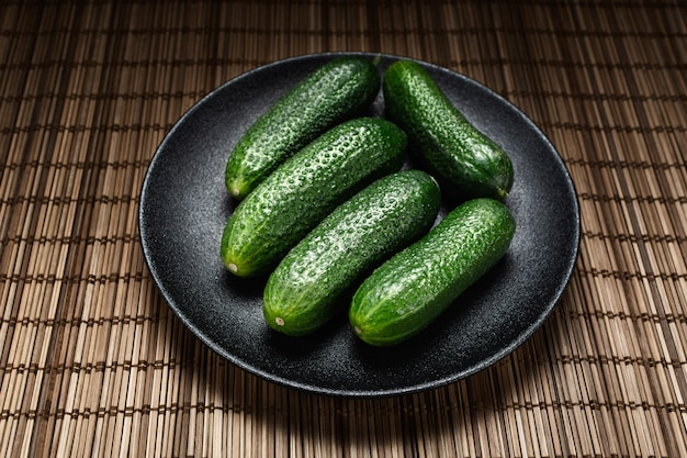 Verse groene komkommer op een grijze plaat