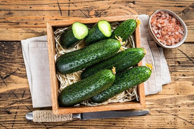 Verse groene komkommers in een houten kist. houten achtergrond. bovenaanzicht.