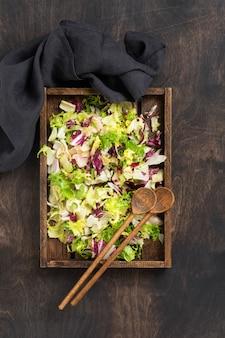 Verse groene lente mix salade bladeren in houten vergiet op houten rustieke achtergrond. selectieve aandacht.