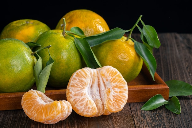 Verse groene mandarijn mandarijn met verse bladeren op donkere houten tafel met zwarte achtergrond oogst concept.