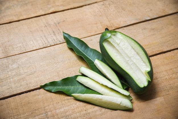 Verse groene mango en groene bladeren op houten