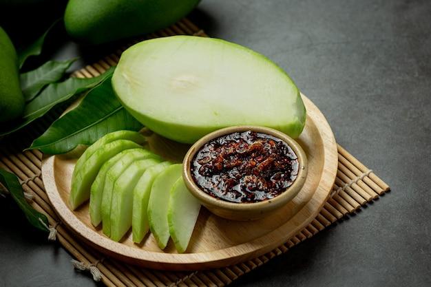 Verse groene mango met zoete vissaus die op donkere oppervlakte dompelt