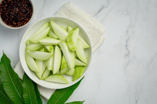 Verse groene mango met zoete vissaus die op witte oppervlakte dompelt