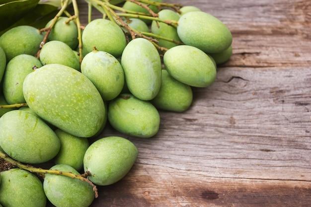 Verse groene mango op houten lijst.
