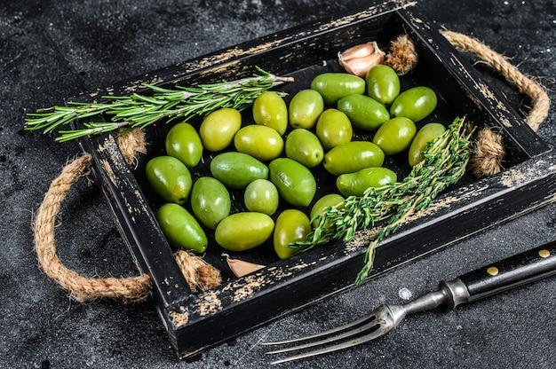 Verse groene olijven in houten bakje met tijm.
