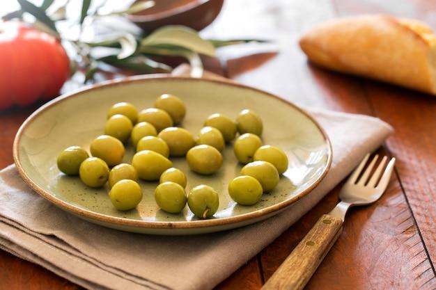 Verse groene olijven op de rustieke plaat