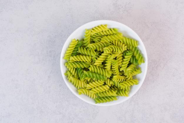 Verse groene ongekookte spiraalvormige macaroni op witte plaat