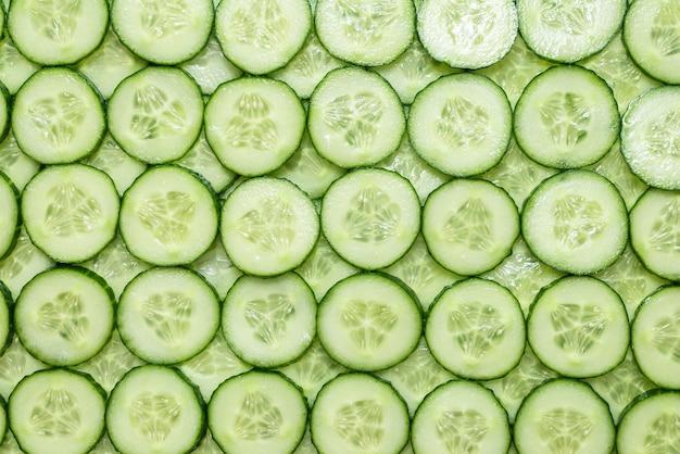 Verse groene plakjes komkommer als achtergrond. bovenaanzicht.